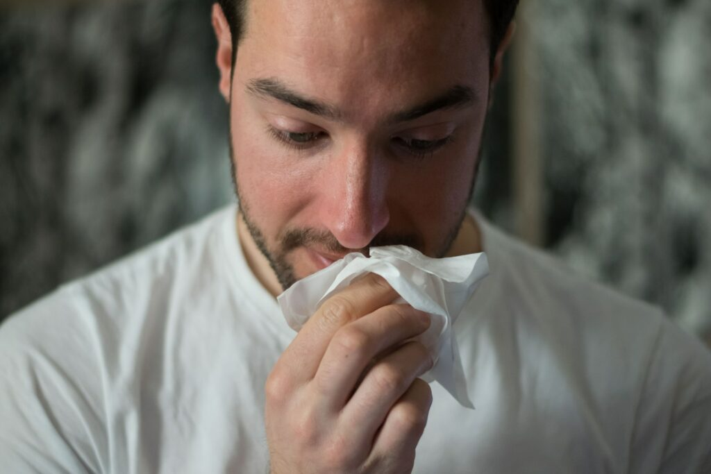 A man wiping his nose.